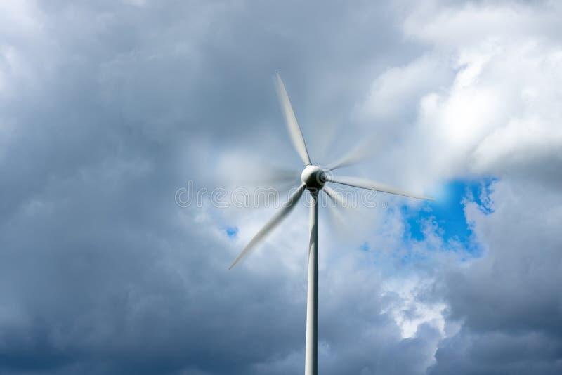 Väderkvarn för vindturbin med rörelsesuddighet och molnig himmel arkivbilder