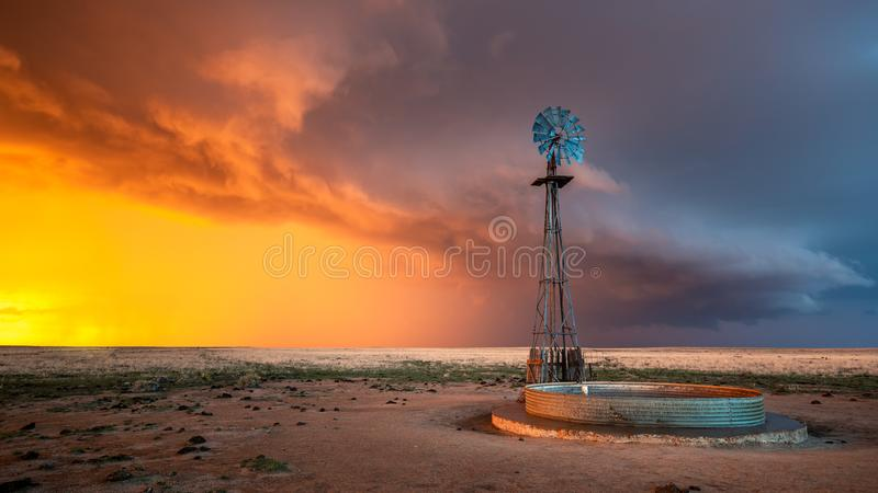 Väderkvarn i en åskväder på solnedgången royaltyfri foto