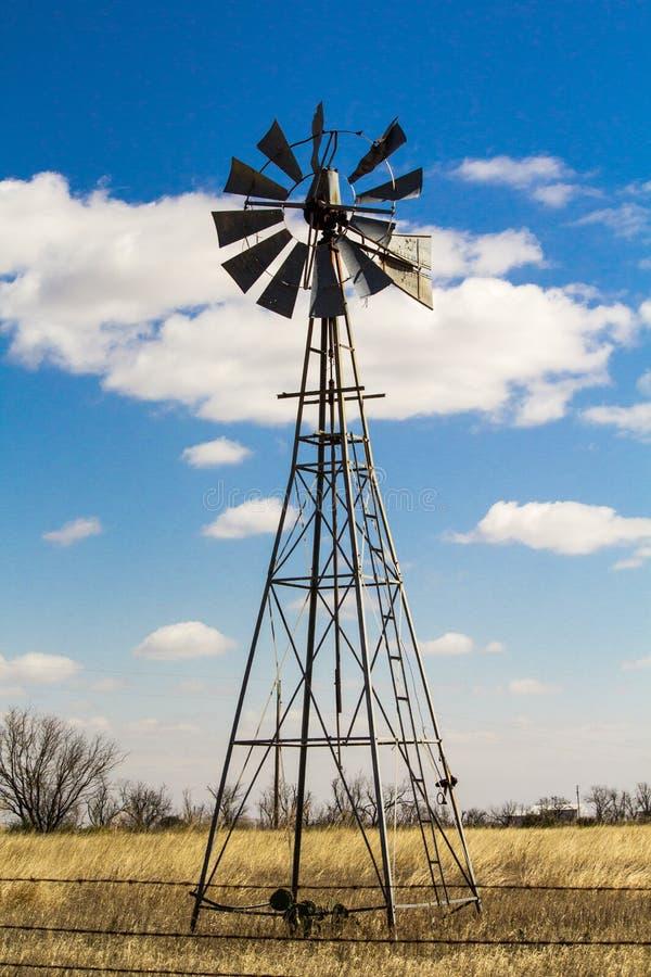 Väderkvarn i mitt av vetefältet arkivbild