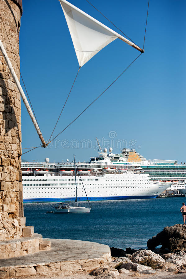 Väderkvarn med kryssningskeppet i bakgrunden royaltyfri bild