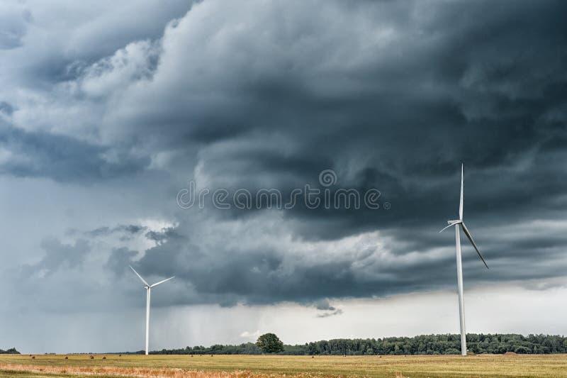 Väderkvarn med stormig himmel Molnig himmel över vetefältet arkivfoto