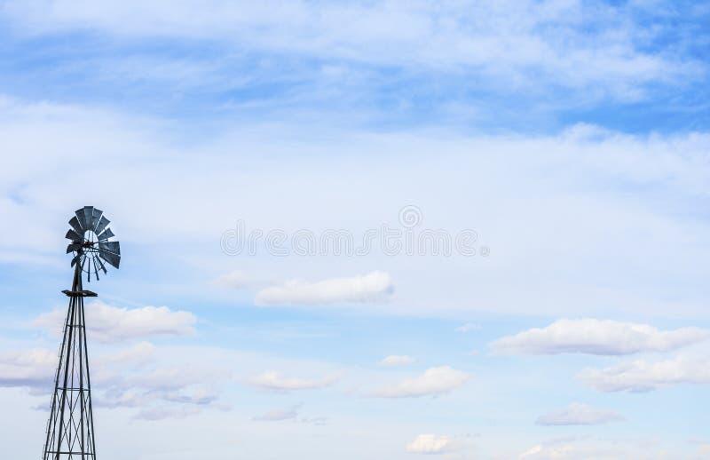 Väderkvarn mot blå molnig himmel arkivbild
