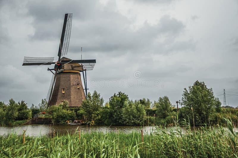 Väderkvarn och högväxta buskar på banken av en stor kanal i en molnig dag på Kinderdijk arkivfoton