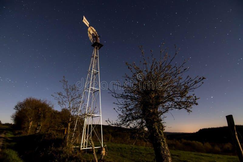 Väderkvarn och månsken royaltyfri foto