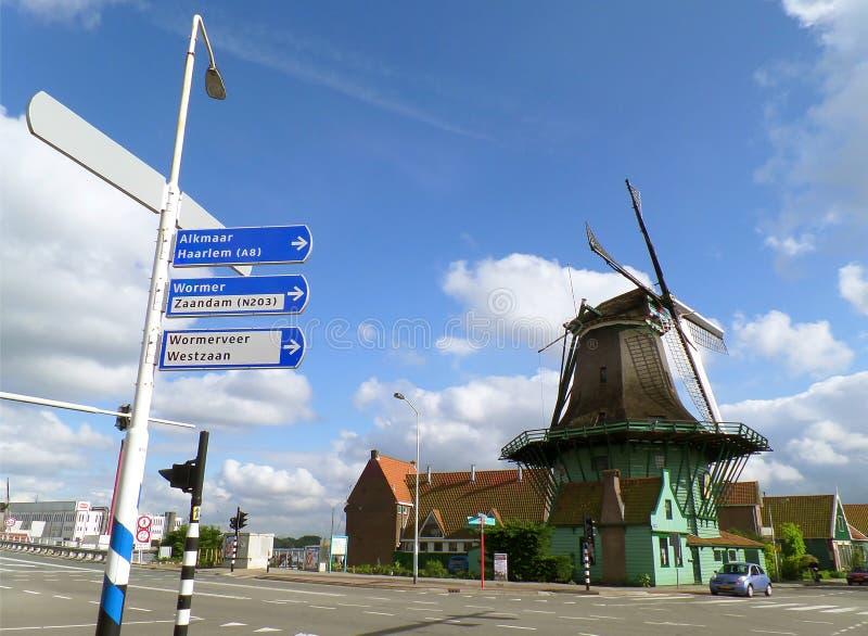 Väderkvarn och vägvisare på trottoaren av Zaanstad, historisk plats i Nederländerna arkivbilder