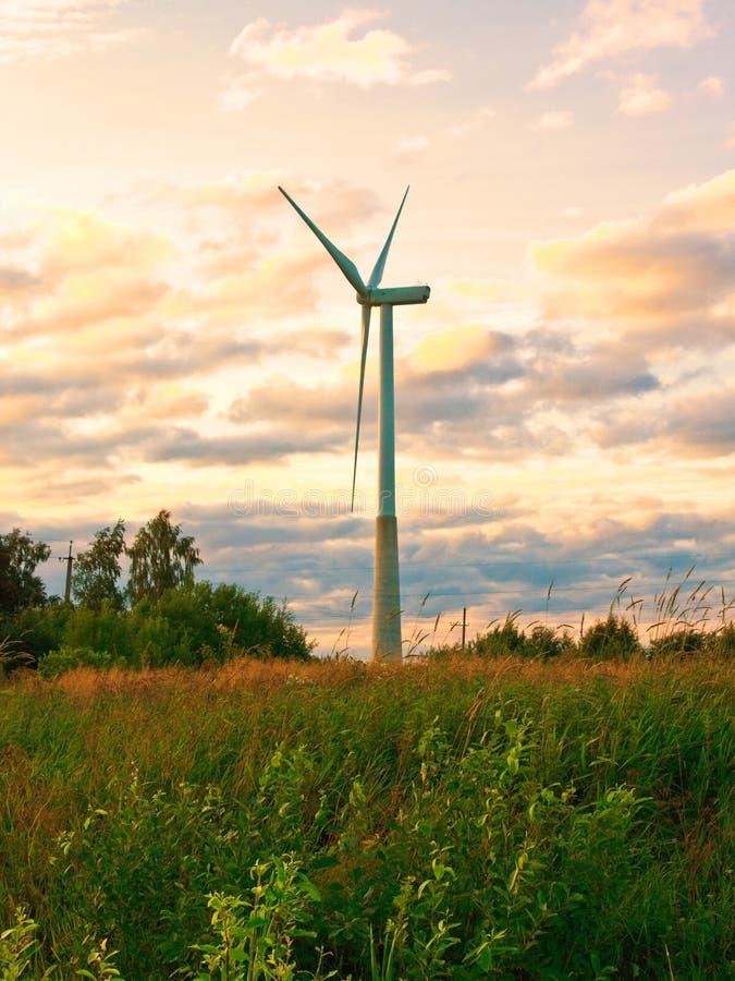 Väderkvarn på lantligt fält i solnedgången för lantgårdkälla för alternativ energi wind för turbiner arkivfoton