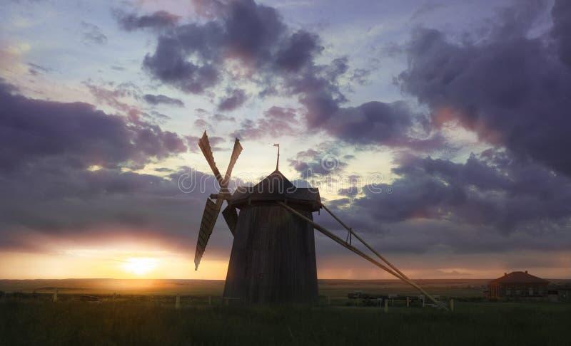 Väderkvarn på soluppgång i Nederländerna Härlig gammal holländsk väderkvarn, grönt gräs, staket mot färgrik himmel med moln fotografering för bildbyråer