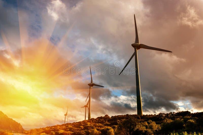 Väderkvarnar för elkraftproduktion i berg royaltyfri fotografi