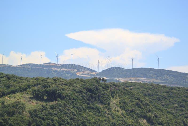 Väderkvarnar för elkraftproduktion på berget royaltyfri bild