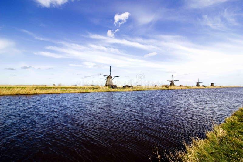 Väderkvarnar vid floden royaltyfri foto