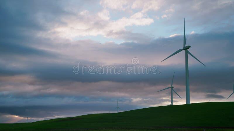 Väderkvarnturbinerna är närbilden mot bakgrunden av åskvädermoln royaltyfria foton