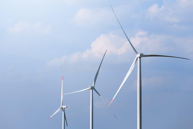Väderkvarnturbinlantgård med delvis molnig blå himmel i bakgrund Förnybara energikällorvindturbiner royaltyfri fotografi