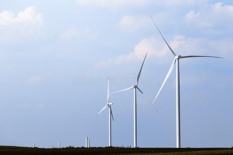 Väderkvarnturbinlantgård med delvis molnig blå himmel i bakgrund Förnybara energikällorvindturbiner arkivfoton