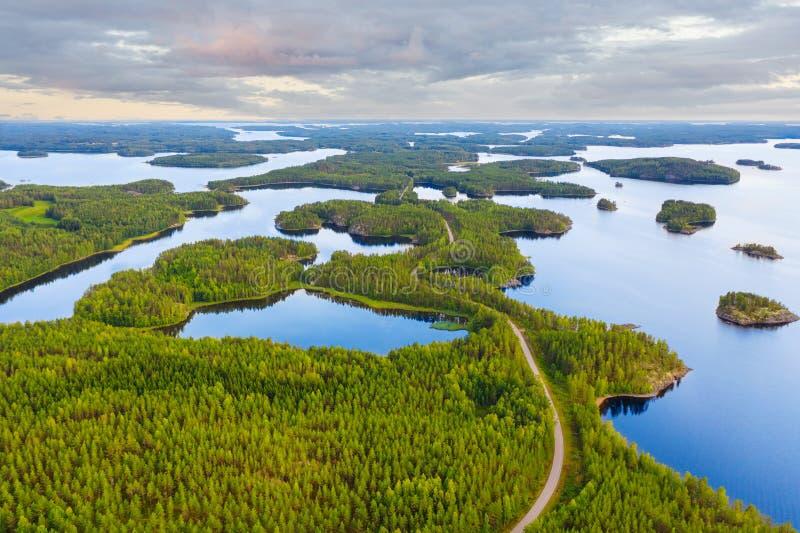 Vädersyn mellan grön sommarskog och blå sjö i Finland arkivfoton