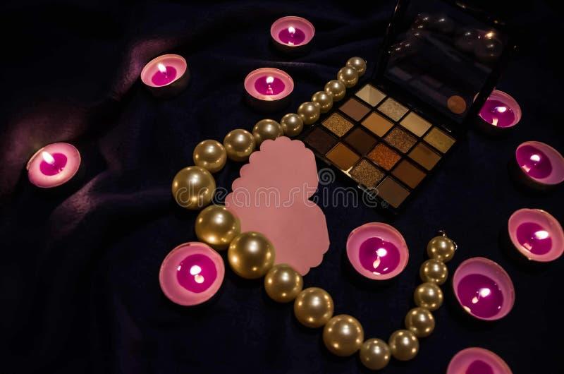 Vädrade stearinljus, en palett av skuggor, en hjärta och härliga pärlor på en filt royaltyfri foto