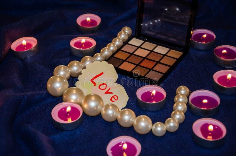 Vädrade stearinljus, en palett av skuggor, en hjärta och härliga pärlor på en filt royaltyfri bild
