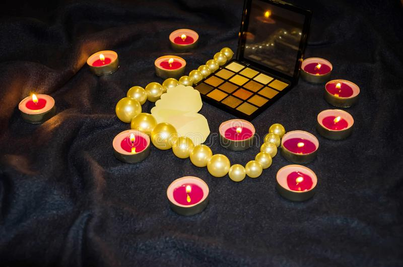 Vädrade stearinljus, en palett av skuggor, en hjärta och härliga pärlor på en filt arkivfoto