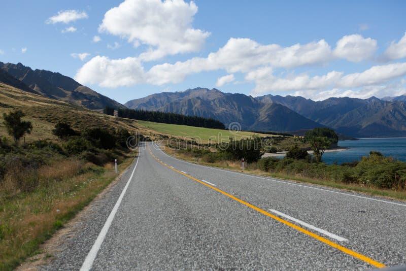 Väg för asfalthuvudvägkurva till bergkocken New Zealand med clo arkivfoto