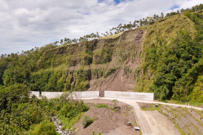Väg med konkreta staket på den Camiguin ön, Filippinerna Skydd av vägen från rockfalls och jordskred fotografering för bildbyråer