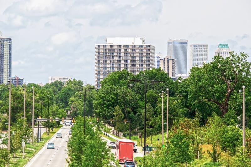 Väg med skilda vägbanor med massor av frodig lövverk och grönt rött ljus med bilar och lastbilar och gångare som leder till i sta arkivbild