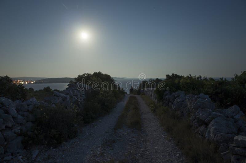 Väg och måne på natten i Dalmatia Kroatien arkivfoto