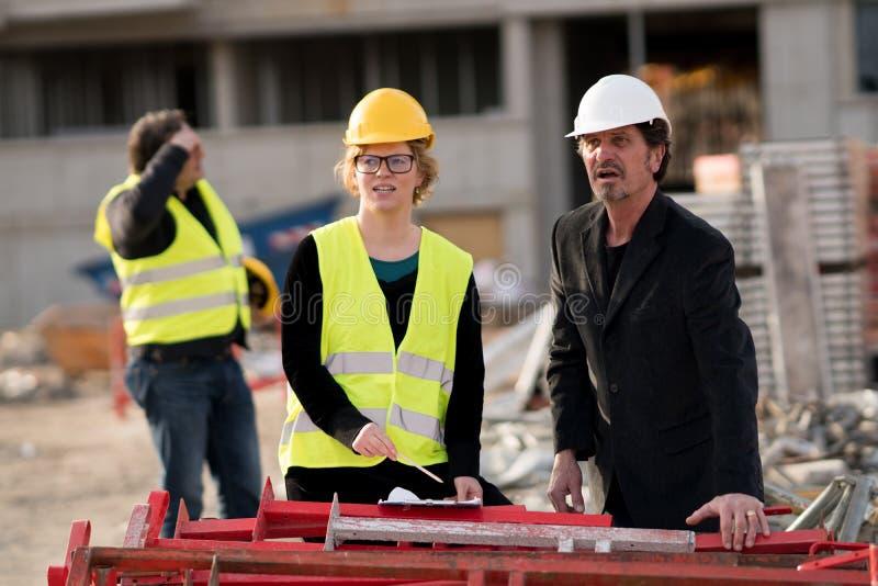 Väg-och vattenbyggnadsingenjör en man och en kvinna, på arbete på konstruktionsplats royaltyfria bilder