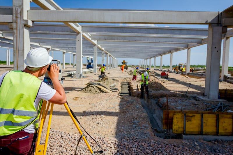 Väg-och vattenbyggnadsingenjör geodet arbetar med den sammanlagda stationen på en byggandeplats royaltyfria foton