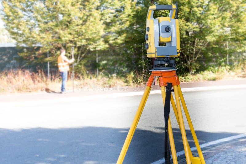 Väg-och vattenbyggnadsingenjör på konstruktionsplatsen genom att använda en tacheometer för altometerinspektörutrustning utomhus fotografering för bildbyråer