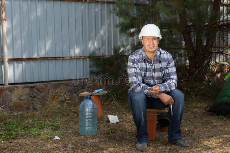 Väg-och vattenbyggnadsingenjör Sitting på hörnet för konstruktionsplats royaltyfri foto