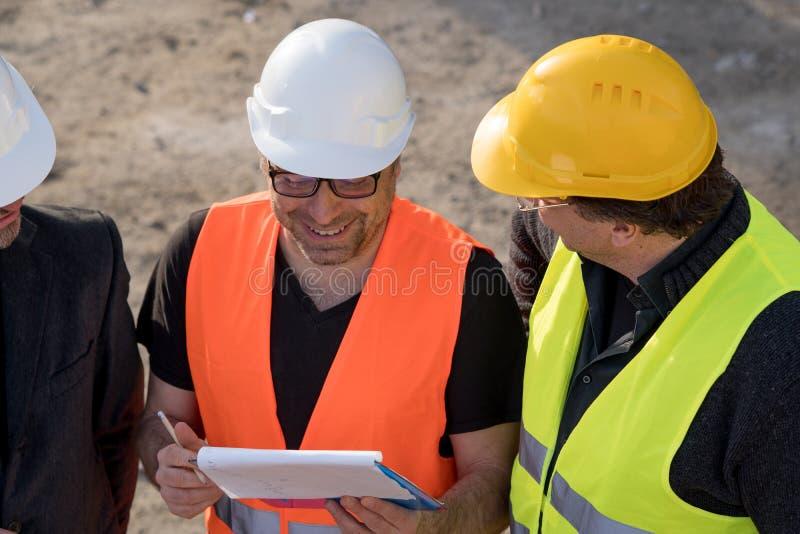 Väg-och vattenbyggnadsingenjör som skriver på en anteckningsbok arkivfoto