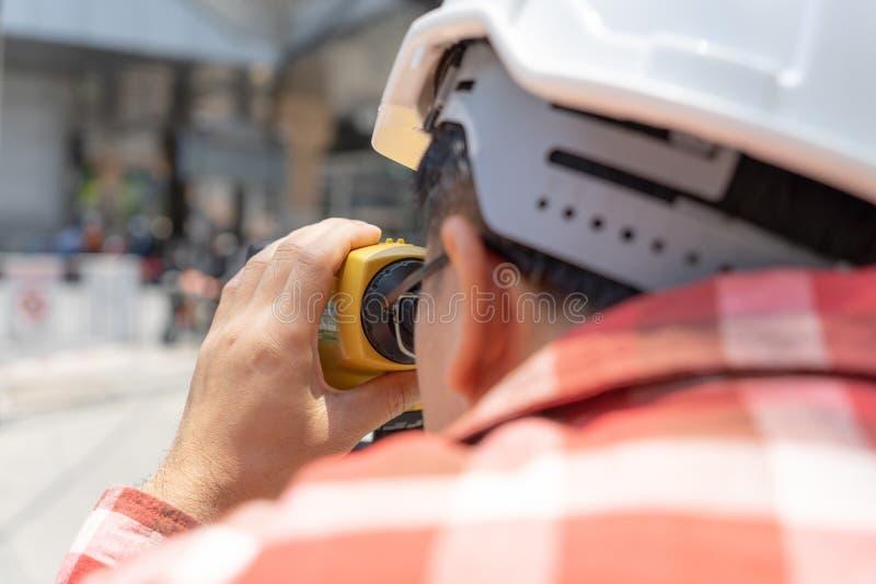 Väg-och vattenbyggnadsingenjörlandgranskning med tacheometer- eller teodolitequipm arkivfoto