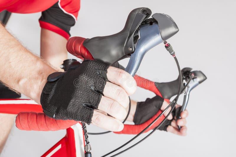 Väg som cyklar sportidéer och begrepp Closeup av idrottsman nen Hands i handskar som rymmer dubbelkontrollspakar royaltyfri fotografi