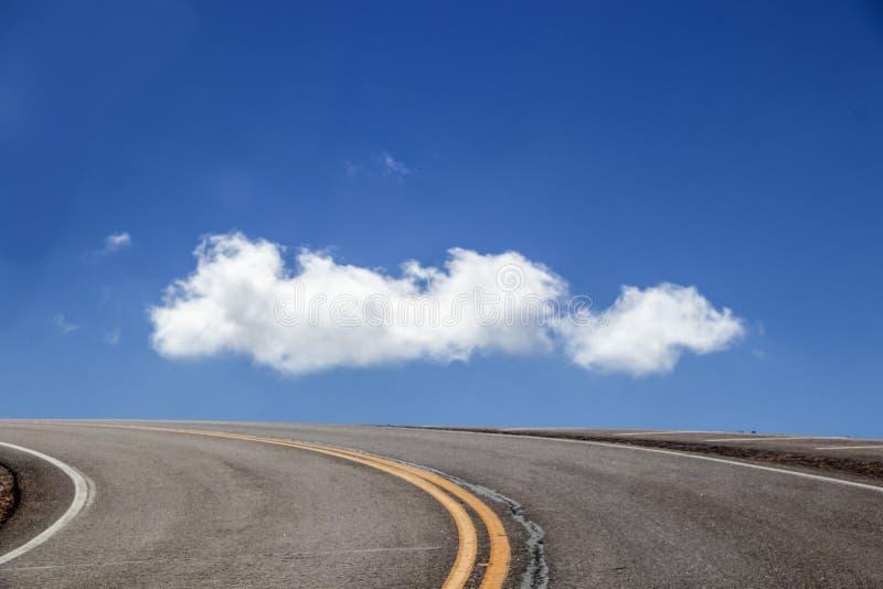 Väg till himlen - kurvan av blacktopvägen med gula bandkörningar runt om berget och alla som du kan se, är en mycket blå himmel o arkivbild