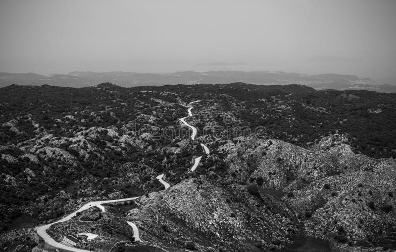 Väg till ingenstans, svartvit bild av vägen bland kullar och fotografering för bildbyråer