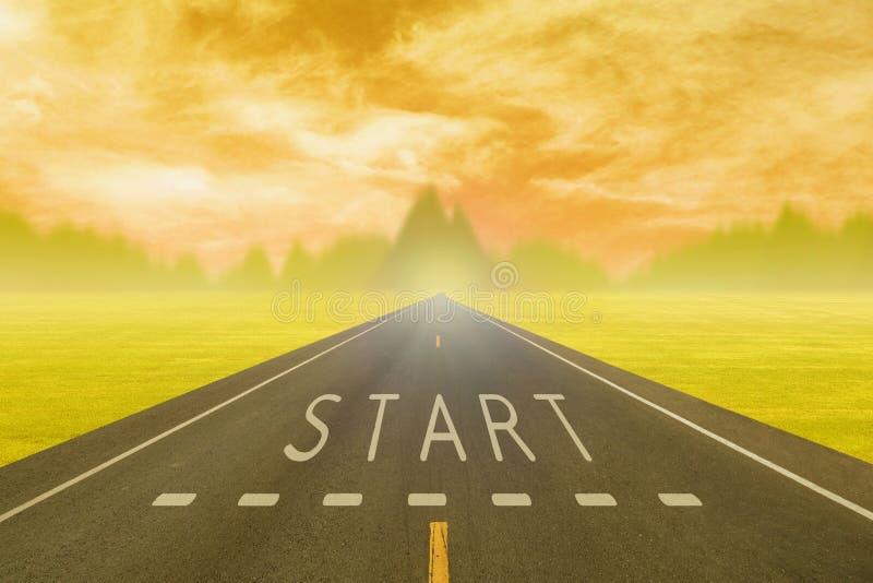 Väg till och med fältet med teckenstart på asfalt på solnedgången royaltyfria bilder