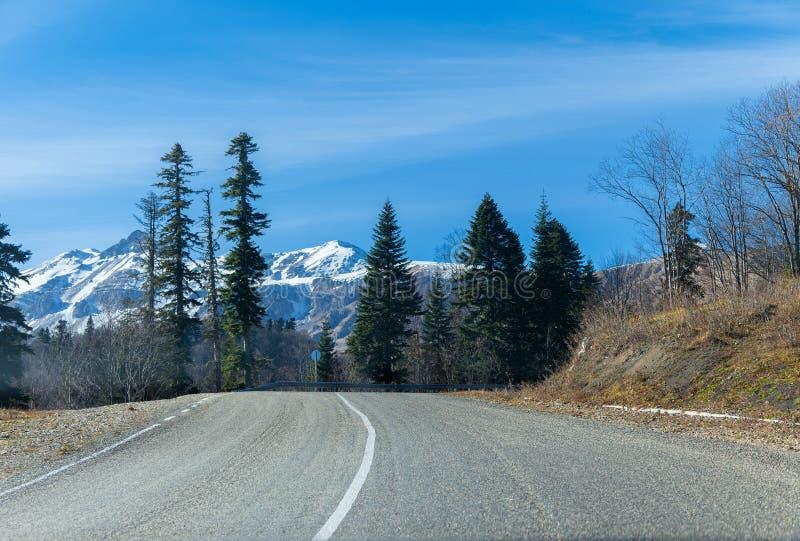 Väg till snöig höjder i berg arkivbild