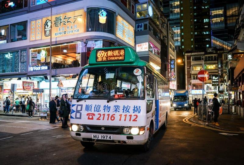 Vägbankfjärd Hong Kong, cityscape för upptagen gata med shoppare, den mini- bussen och bilar royaltyfria foton