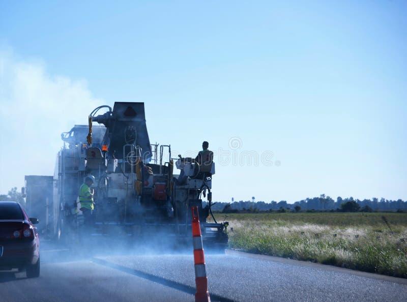 Vägbesättningar applicerar asfalt till Blacktop en huvudväg fotografering för bildbyråer