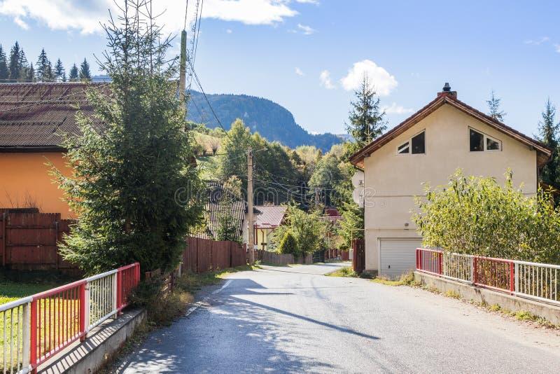 Vägbortgången till och med byn på foten av de Carpathian bergen nära staden av kli i Rumänien royaltyfria foton
