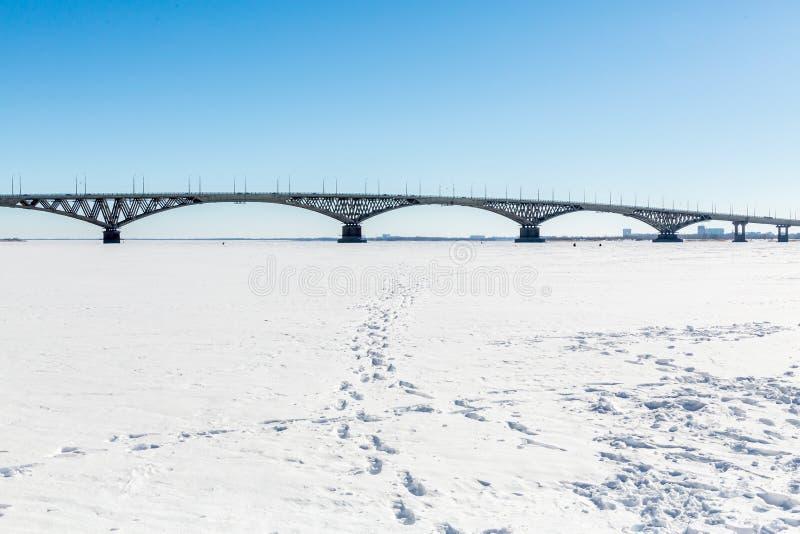 Vägbro över Volgaet River mellan städerna av Saratov och Engels övervintrar trees för snow för sky för lies för frost för mörk da royaltyfria bilder
