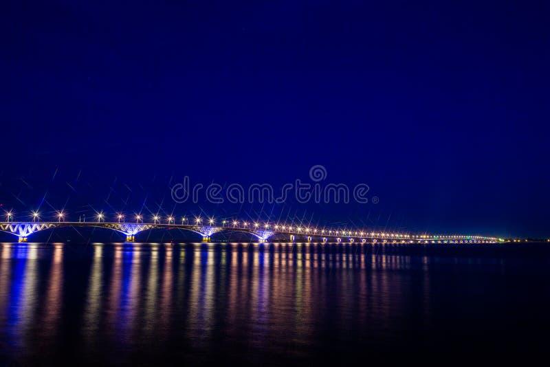 Vägbro över Volgaet River mellan städerna av Saratov och Engels, Ryssland Natt- eller aftonlandskap fotografering för bildbyråer