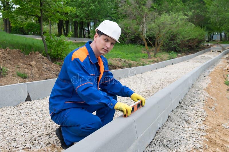 Vägbyggmästaren kontrollerar riktigheten av arbetet bar ut genom att använda den byggande nivån royaltyfri bild