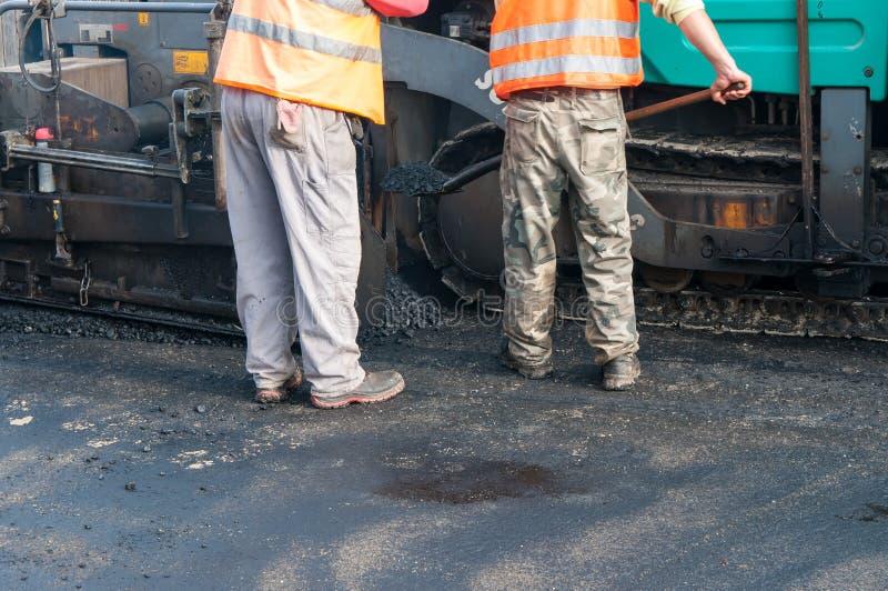Vägbyggnadsarbetare som asfalterar maskineri arkivbild