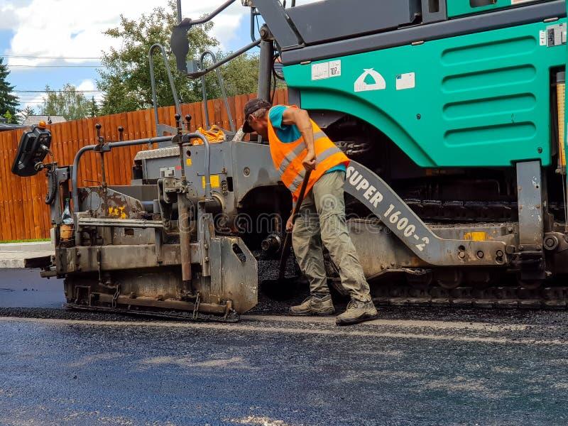 Vägbyggnadsarbetare som skyfflar den varma asfalten royaltyfria foton
