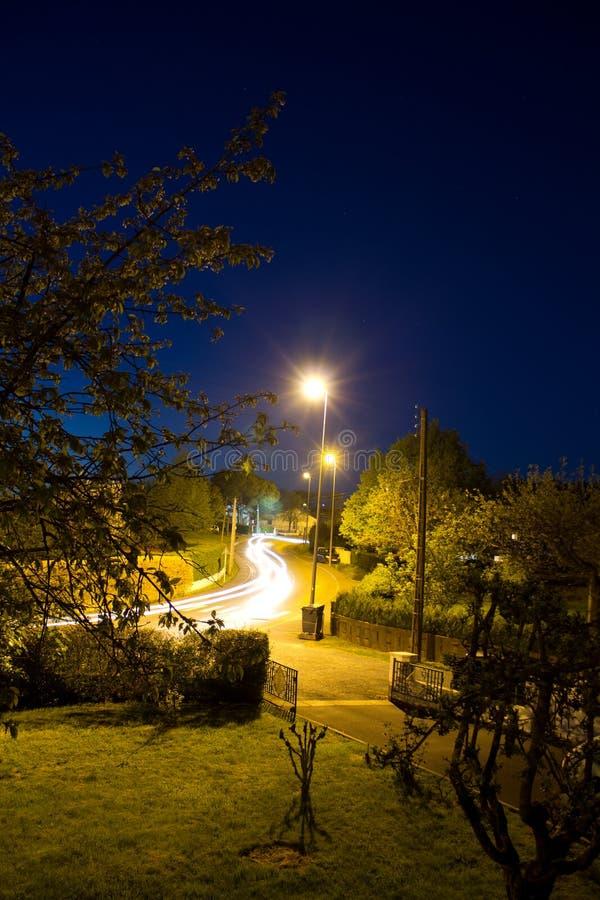 Vägen i gataljus på natten i lång exponering som kör bilar, tänder målning royaltyfria foton