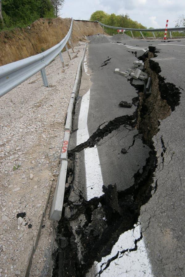 Vägen kollapsar med enorma sprickor Den internationella vägen kollapsade ner efter dålig konstruktion Skadad huvudvägväg för bild arkivbild