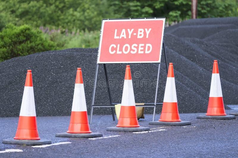 Vägen lägger undan det stängda tecknet med högen av svart tjära och röda trafikkottar fotografering för bildbyråer