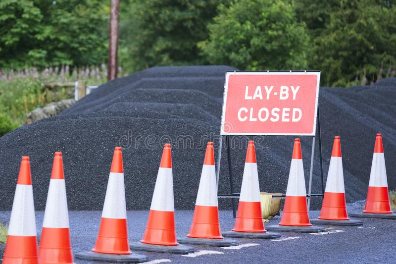 Vägen lägger undan det stängda tecknet med högen av svart tjära och röda trafikkottar royaltyfri foto