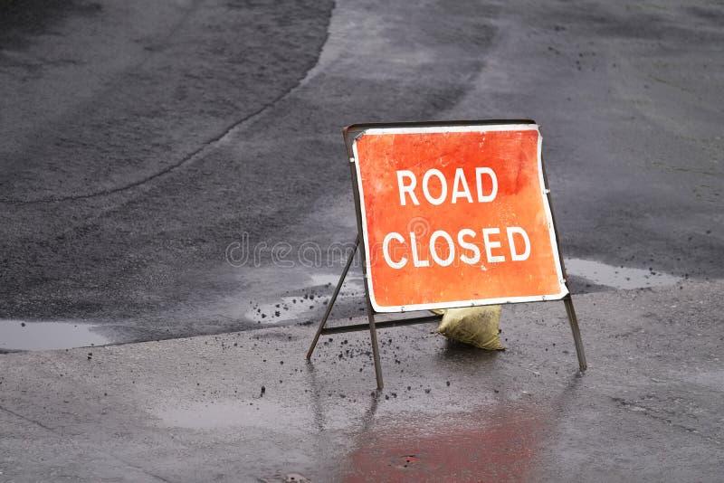 Vägen stängde det röda tecknet och den svarta tjäraasfaltgatan arkivfoto