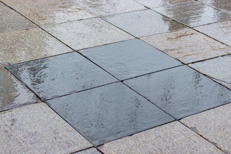 Vägens stadsyta är våt, gatan är kantad med kvadratiska grå, svarta granitplattor Väteasfalt, regnigt väder royaltyfri bild
